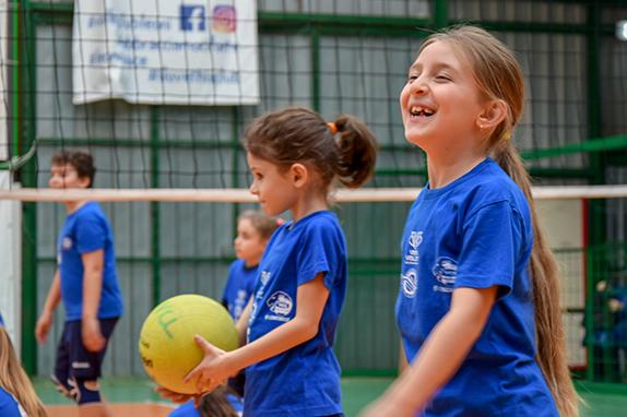 bambina che sorride giocando a pallavolo